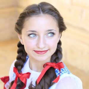 "Portrait image of girl wearing costume with red ribbon in her hair modeling ""Dorothy Braids"" hairstyle"