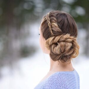 """Back view of a girl in a purple shirt, standing outside modeling a """"Stacked Fishtail Updo"""" hairstyle"""