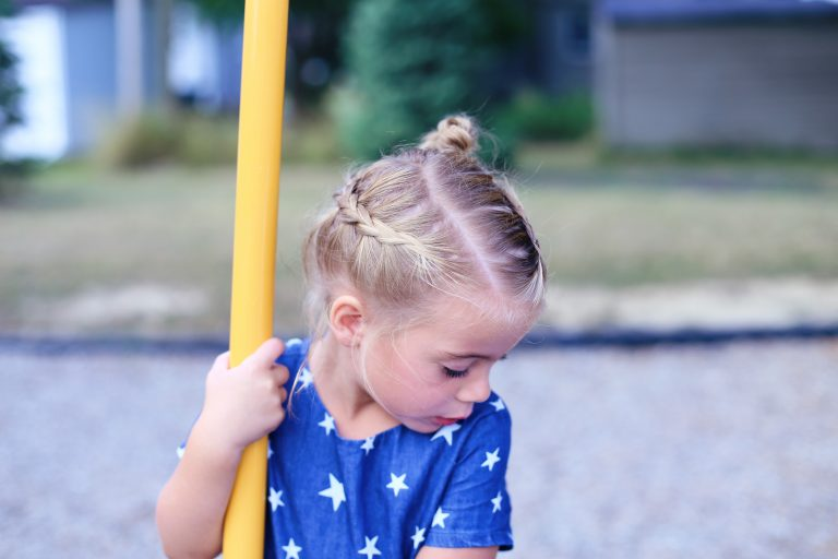 """Little girl wearing blue shirt with white stars and playing outside modeling the """"Crown Braid"""" hairstyle."""