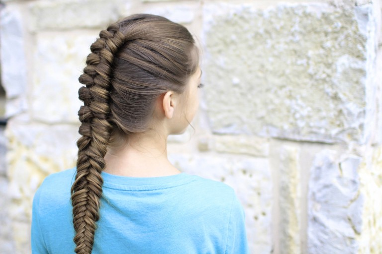 """Side view of girl in a blue shirt standing outside modeling """"Infinity Braid Combo"""" hairstyle"""