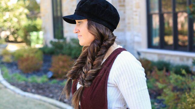 "Profile view of Mindy Mcknight standing outdoors modeling the ""Fluffy Faux Fishtail"" braids"