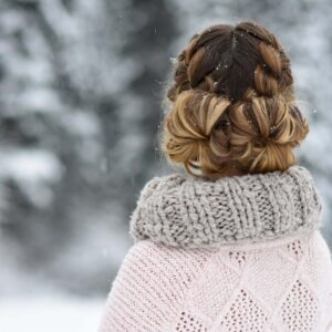 "back view of girl standing outside in the snow while modeling "" Double French Buns"" hairstyle."