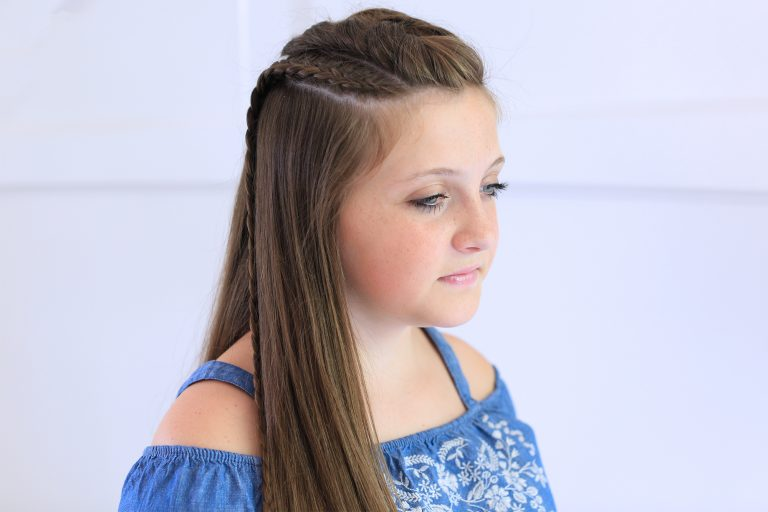"Side view of girl with blue shirt standing indoors modeling the ""Dutch Lace Braid Combo"" hairstyle"