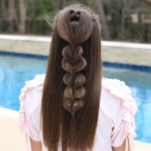 "Back view of girl standing outside in front of the pool modeling the ""Heart Pull-Thru Braid"" hairstyle"