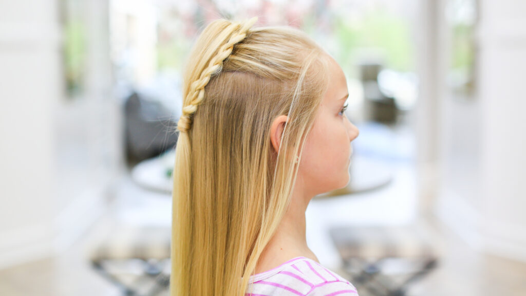 "Profile view of girl with long blonde hair standing indoors modeling the ""Fluffy Heart Braid"" hairstyle"