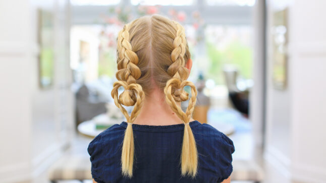 "Back view of blonde girl standing indoors modeling the ""Dutch Heart 2 in 1"" hairstyle with double braids."