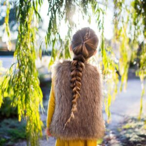 "Back view of girl standing outside in forest modeling the ""Dutch Pull-Thru Combo Braid"" hairstyle"