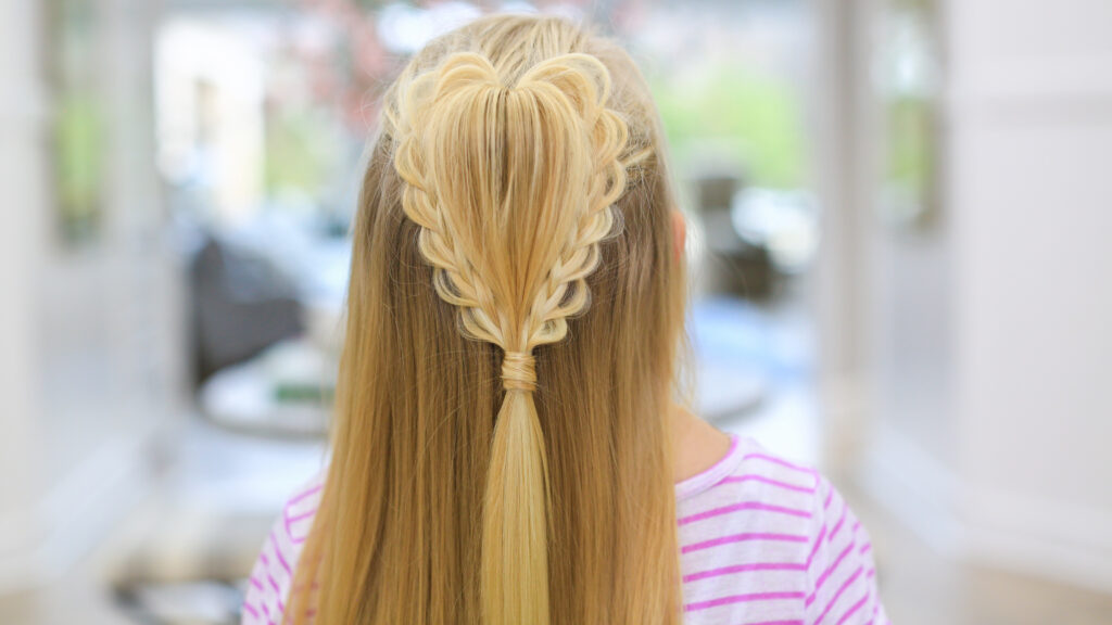 "back view of a girl with long blonde hair standing indoors modeling the ""Fluffy Heart Braid"" hairstyle"