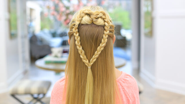 "back view of a girl with long blonde hair standing indoors modeling the ""Mermaid Hair Braid"" hairstyle"