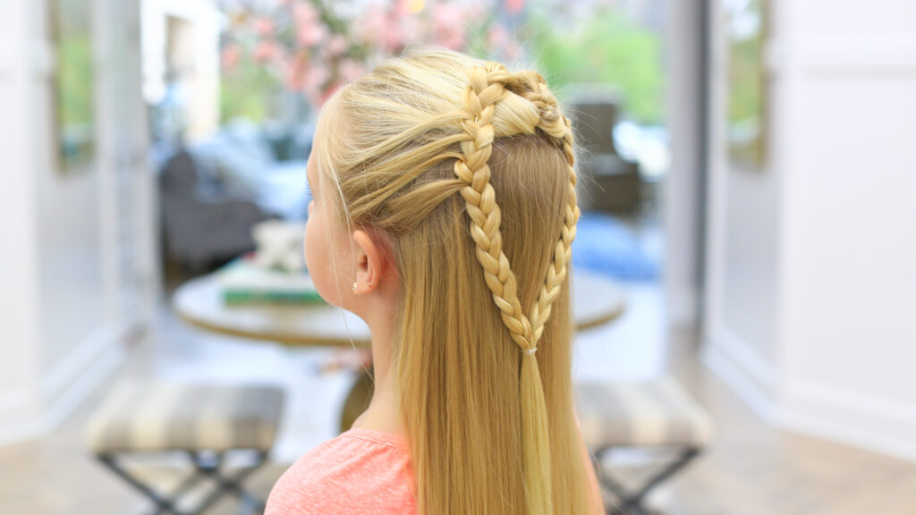 "Side view of a girl with long blonde hair standing indoors modeling the ""Mermaid Hair Braid"" hairstyle"