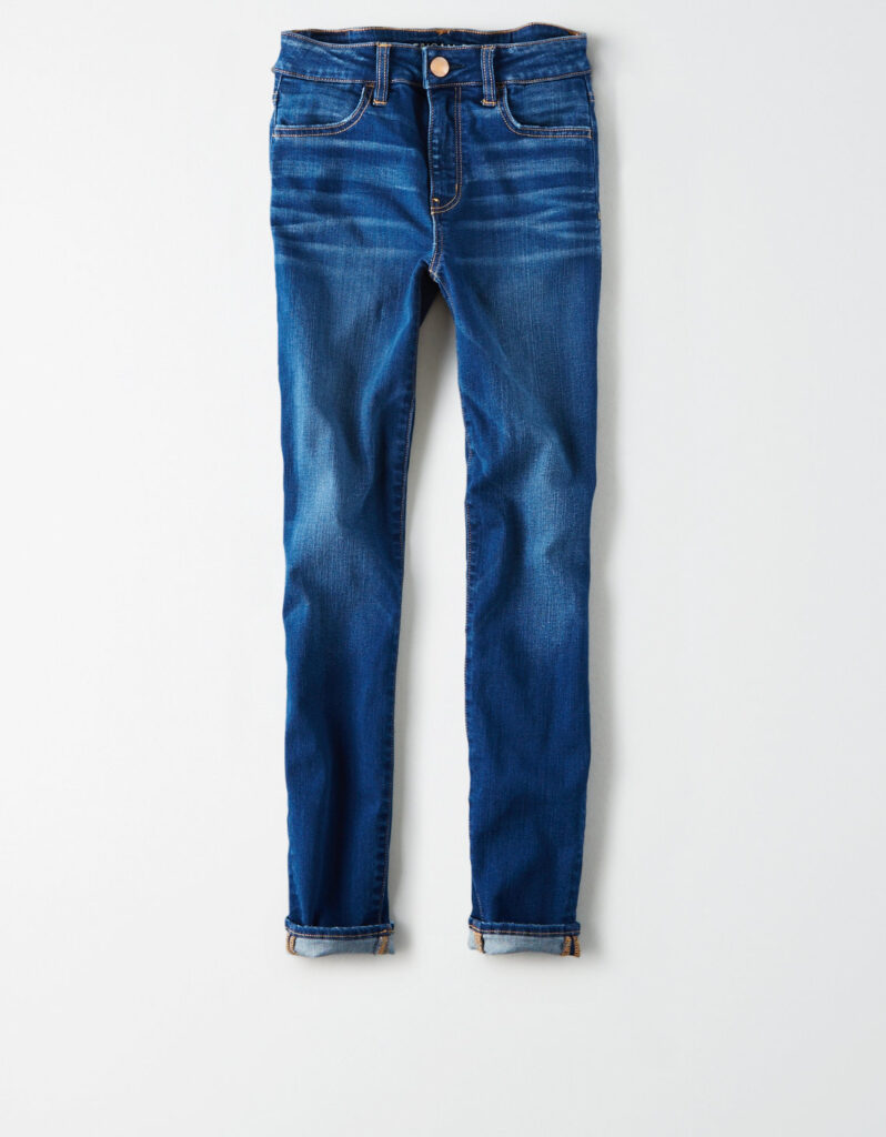 Denim pants folded at the legs in front of a white background