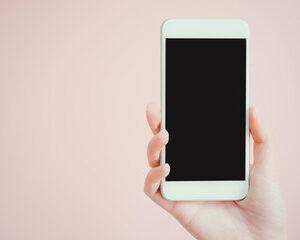 Hand holding a white smart phone in front of a pink background