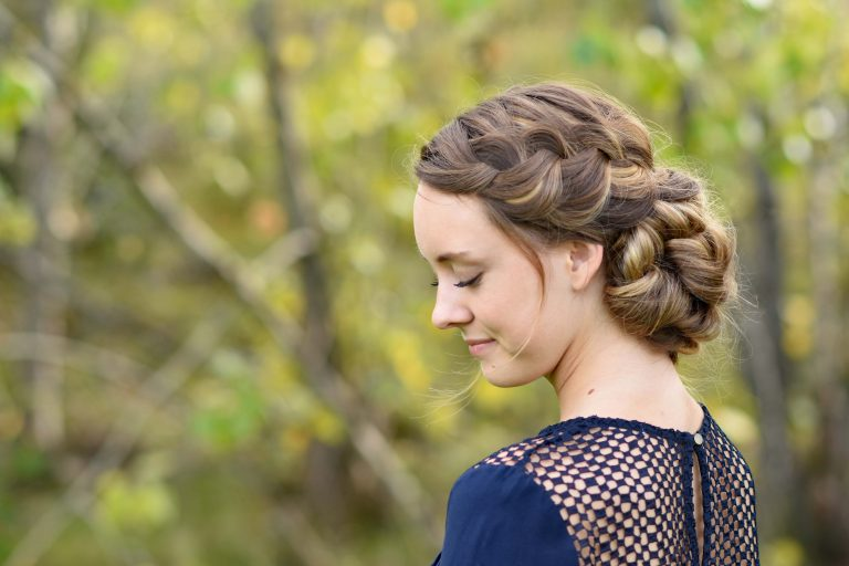 "Side profile of smiling girl looking downwards standing outside modeling the ""French Braid Updo"" hairstyle"