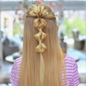 "Back view of a young blonde girl standing indoors modeling the ""Triple Flip Flips"" hairstyle"