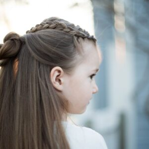 "Side profile for a young girl standing outside modeling ""Braided Bun Combo"" hairstyle"