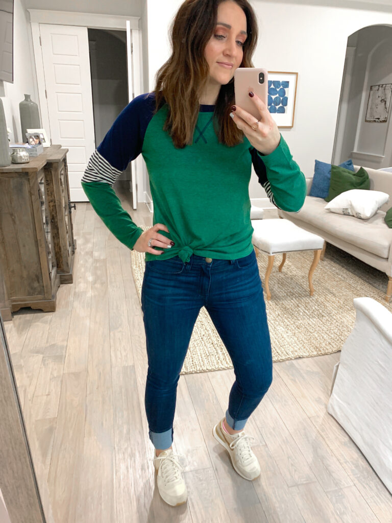 Mindy Mcknight posing in her room while holding a phone up taking a photo