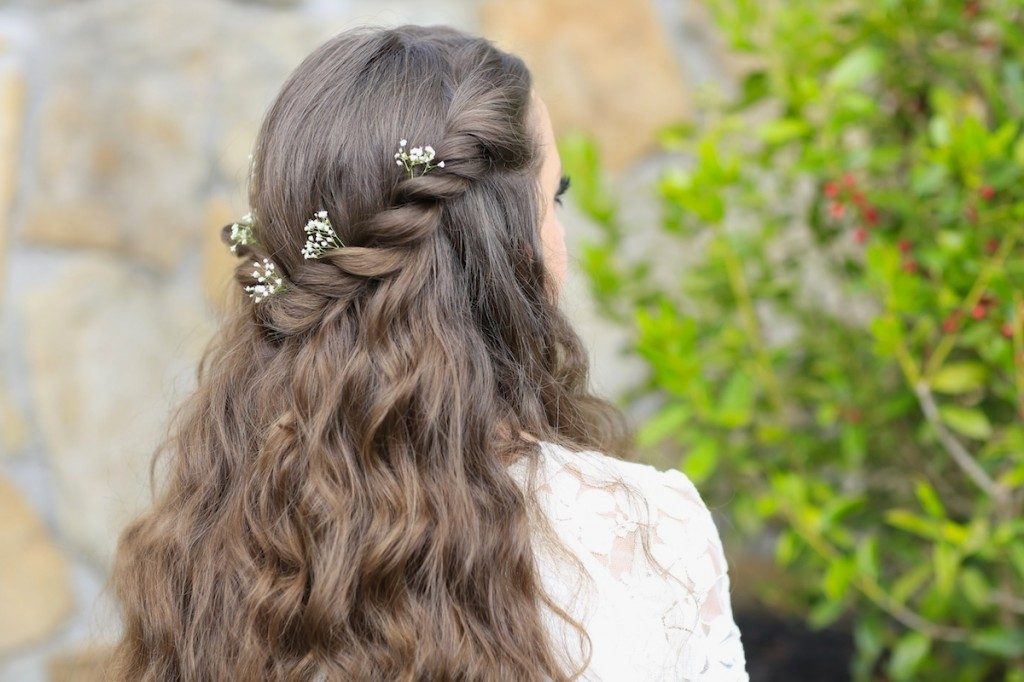 "Back view of girl with flowers in her hair standing outside modeling the ""Aurora Twistback"" hairstyle"