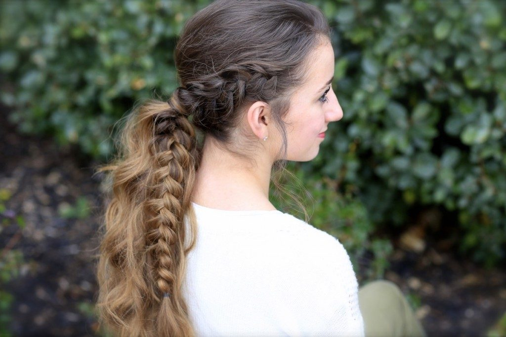 "Side profile image of smiling girl standing in front of outside bushes modeling a ""Viking Braid"""