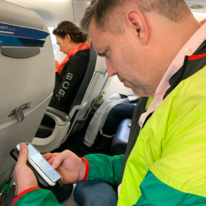 Man on an airplane sitting looking down at his smartphone