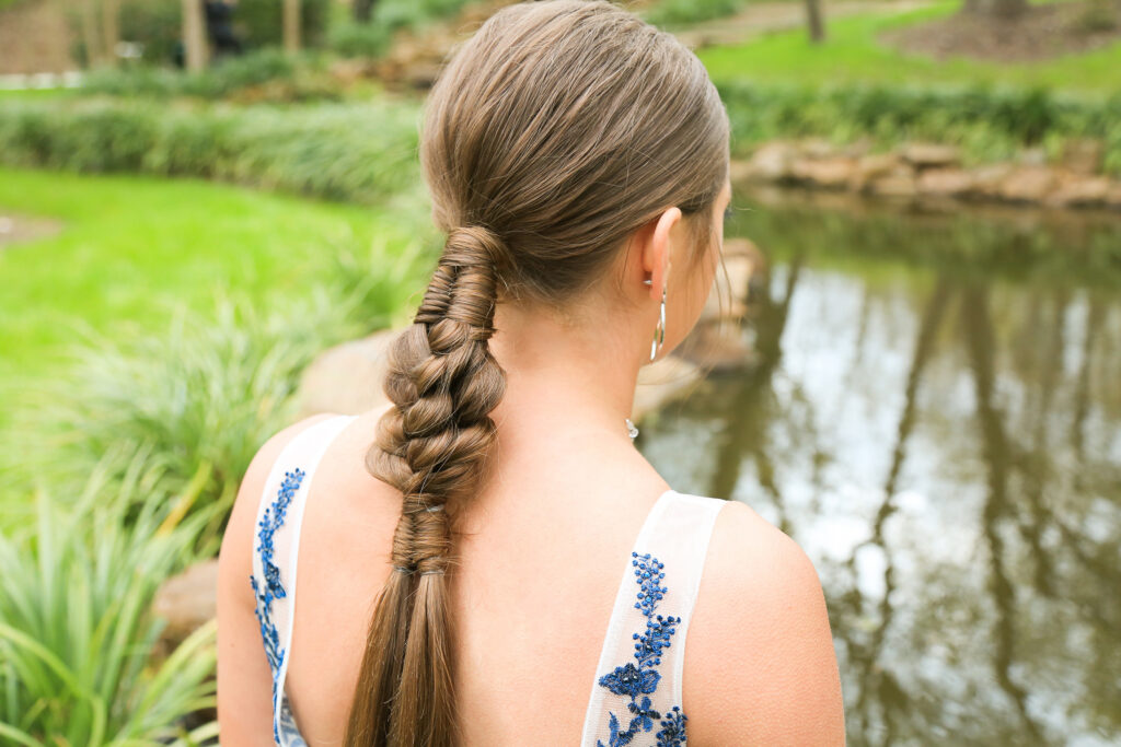 Side view of burnette girl with standing by pond with low infinity braid combo hairstyle.