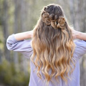 "Back view of girl standing outside in the wooded area modeling the ""Lace Pull-Thru Rosette Bun"" hairstyle"