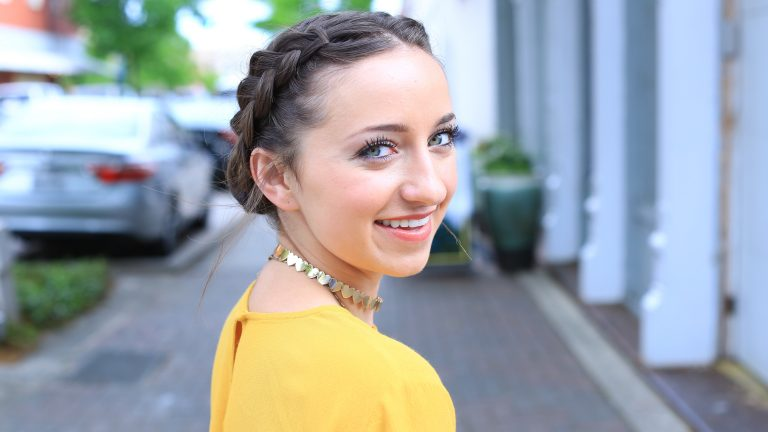 Side profile of girl smiling standing outside modeling a Double Dutch Buns