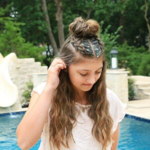 Girl standing by the pool with glitter in her hair modeling Double Dutchbacks into a Messy Bun hairstyle.