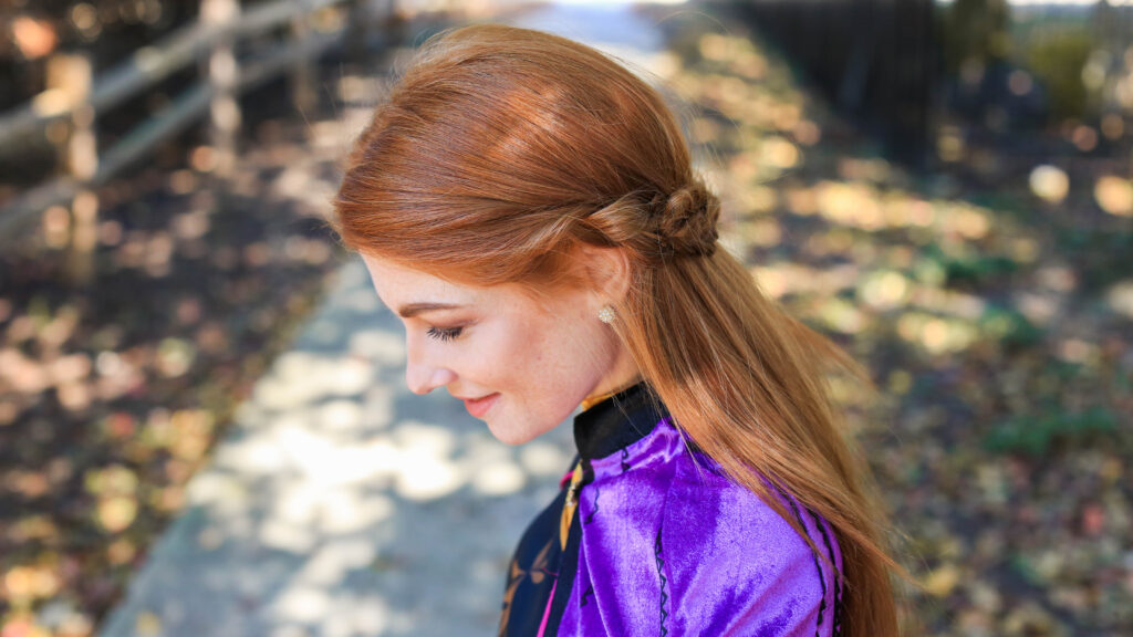Profile view of long hair woman with Frozen inspired back braid hairstyle.