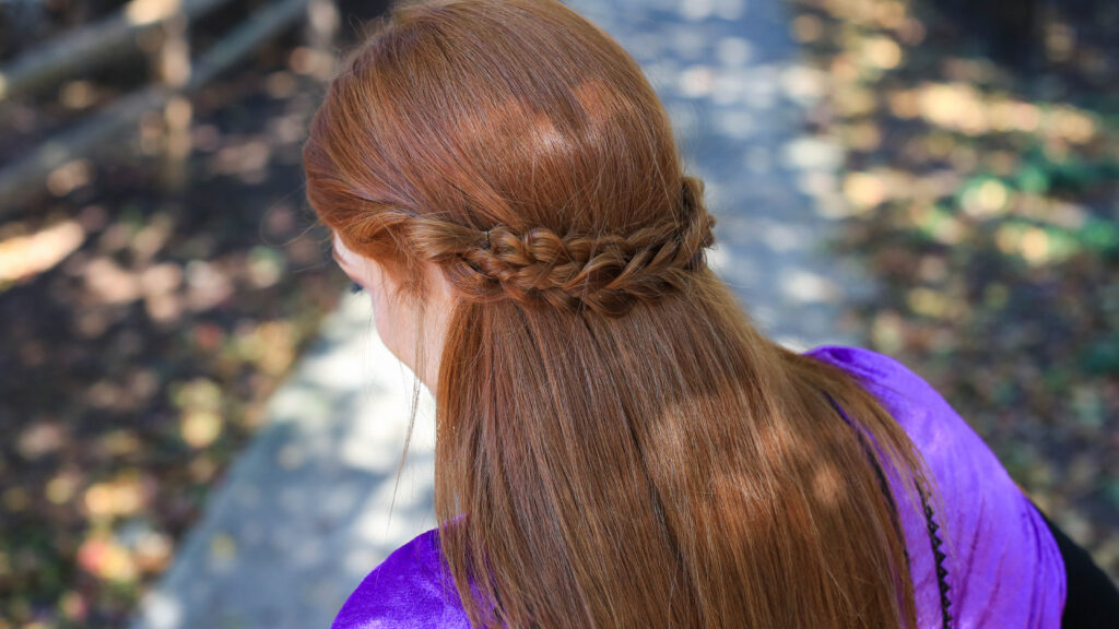 Back view of long hair woman with Frozen inspired back braid hairstyle.