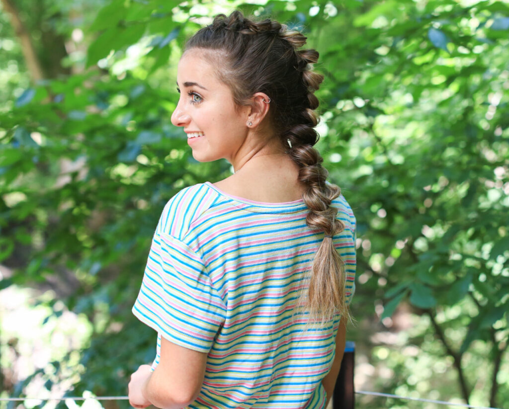 "Side profile view of girl with striped shirt standing outside modeling the ""CGH Wrap Braid"" hairstyle"