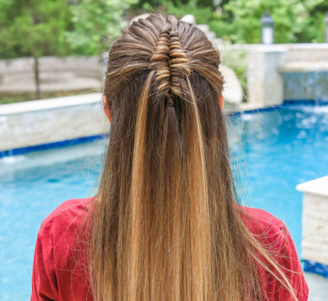 up close view of girl by the pool with long hair and showcasing long infinity braid