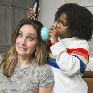 Mother and daughter are testing multiple head massagers on the mother's head.