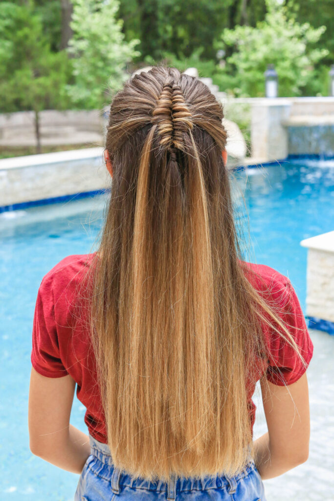 Back view of girl by the pool with long hair and showcasing long infinity braid