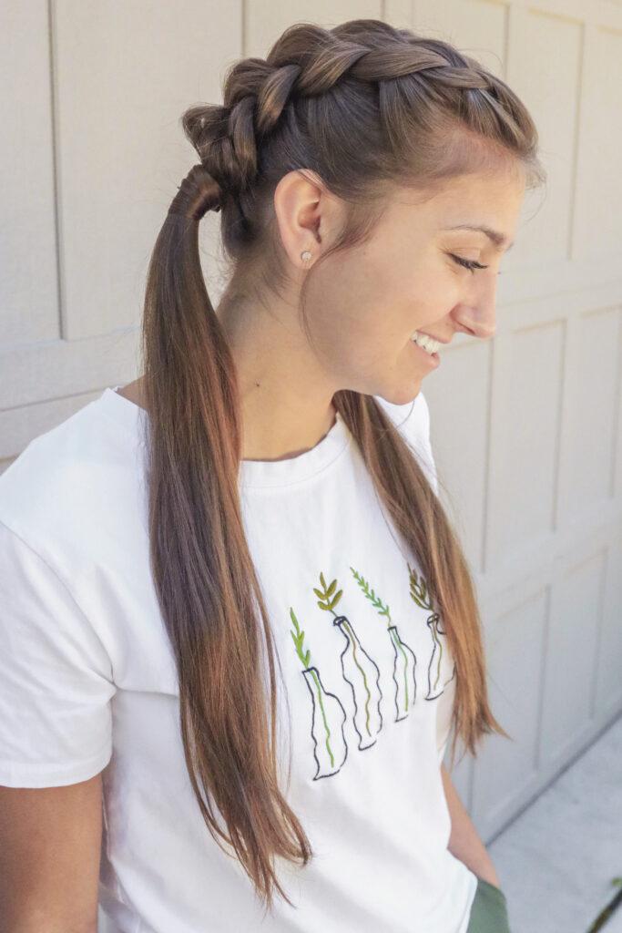 Photo de profil d'une jeune fille aux longs cheveux bruns debout à l'extérieur de la modélisation