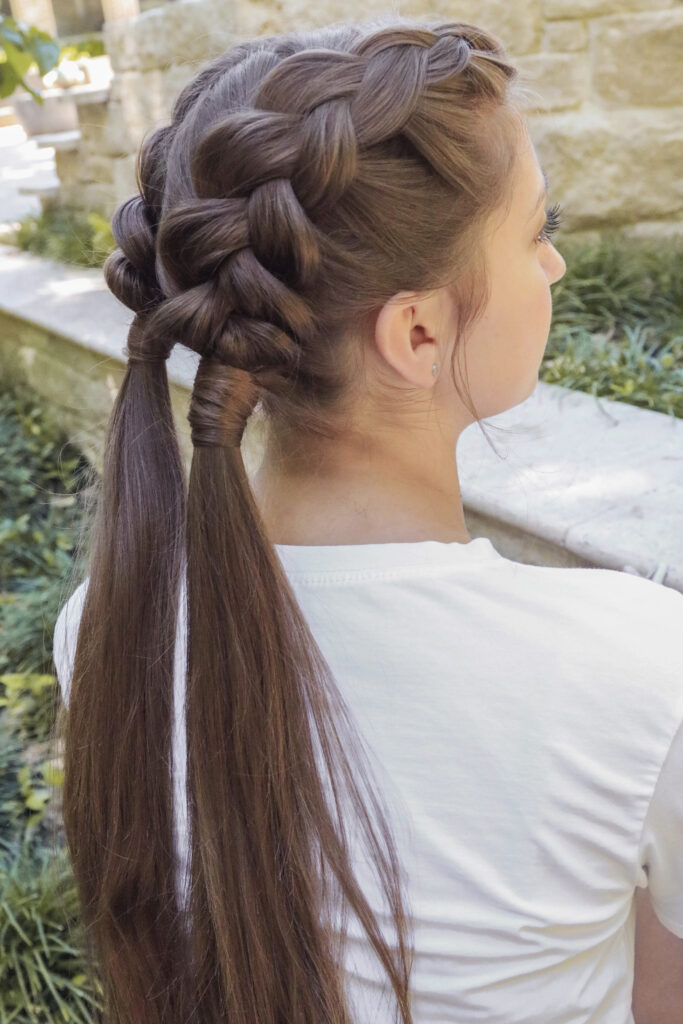 """Profile shot of girl with long brown hair standing outside modeling the """"Double Dutch Wrap"""" hairstyle"""