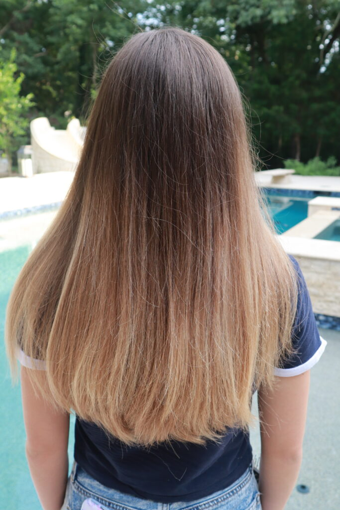 Back side of girl with long straight hair standing outside in front of the pool