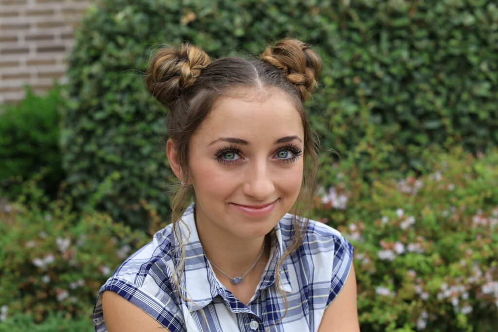 Girl sitting outside modeling Double Braided Bun for back to school hairstyles