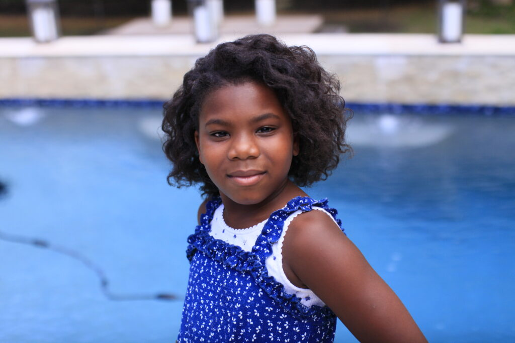 little girl standing by the pool smiling