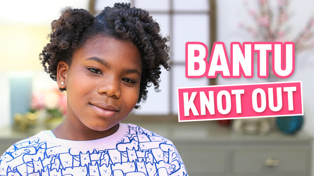 "Young girl smiling at the camera ""Bantu Knot Out"""