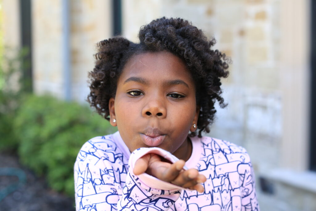 Young girl with Bantu Knots blows a kiss to the camera